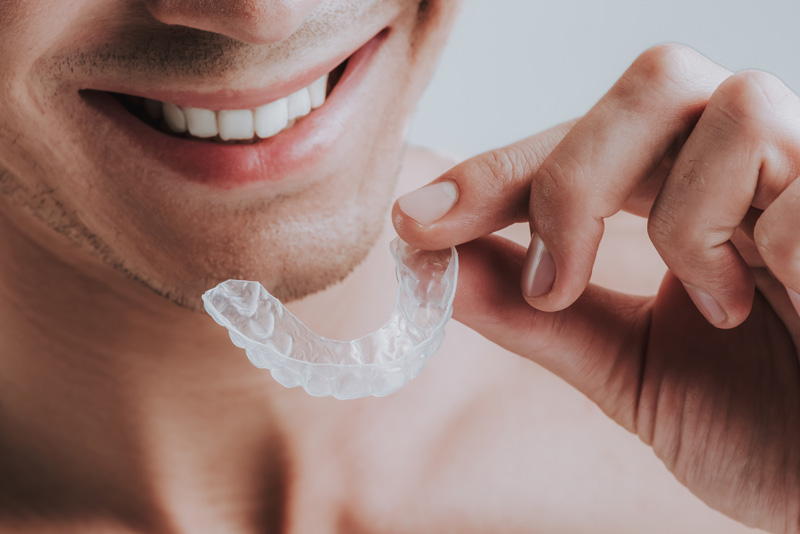 close-up-of-man-holding-transparent-mouth-guard
